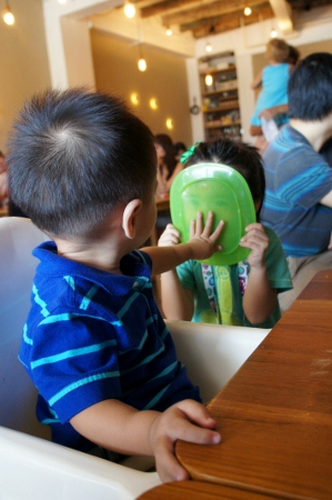 squishing an oily plate against his sister's face