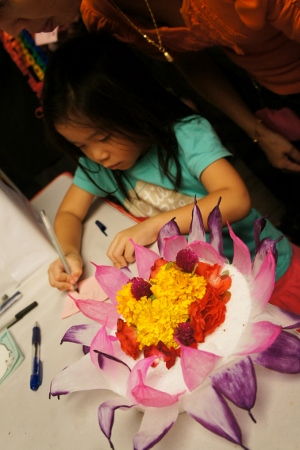 writing a wish for her krathong
