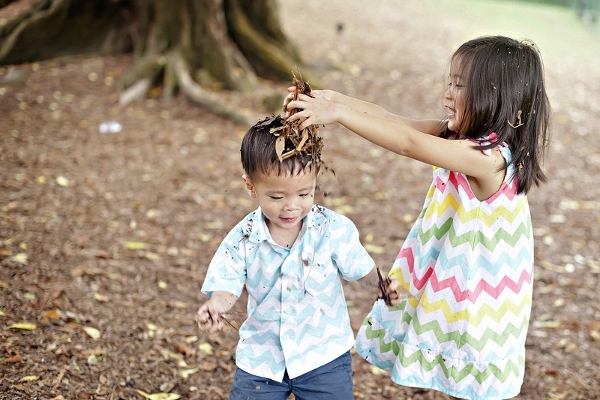 throwing leaves on her brother's head