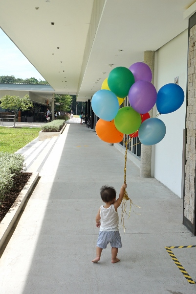 the baby running away with balloons